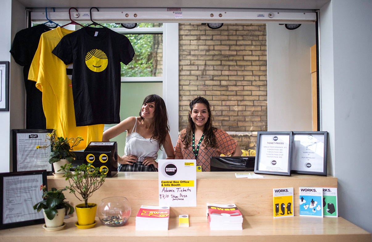 Two young volunteers stand behind a counter full of SummerWorks books and merchandise