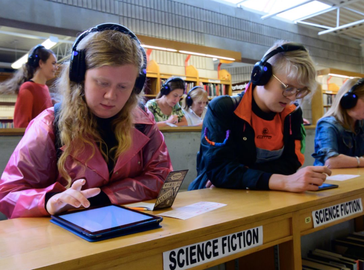 Young people in classroom using tablets with headphones.
