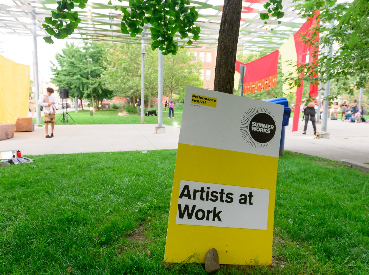 A sign posted in a city park that reads Artists At Work
