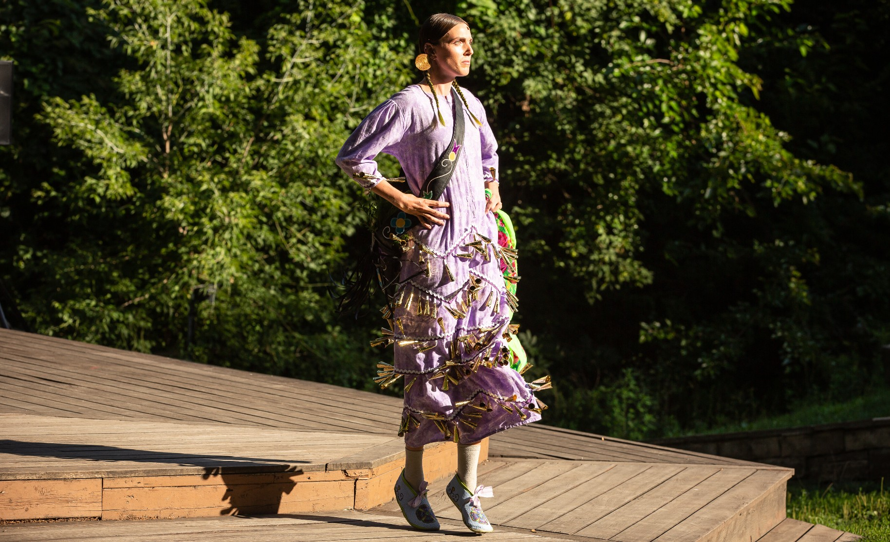 A performer stands on their toes at the edge of a wooden stage surrounded by trees. They are wearing a light purple dress with many small bells sewn onto the lower half, their long brown hair is in braids.