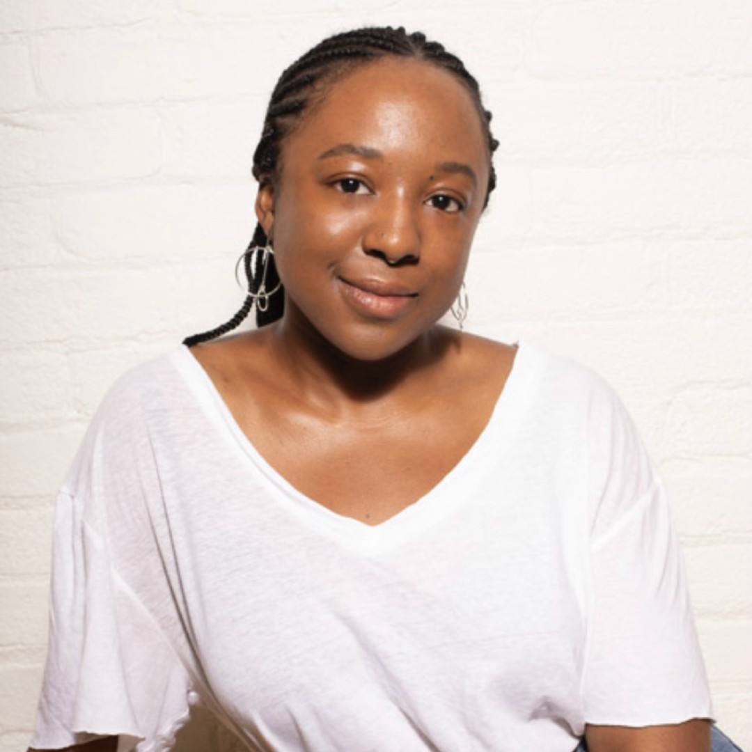 A young Black woman with long hair pulled back in braids wearing a white t-shirt smiling at the camera