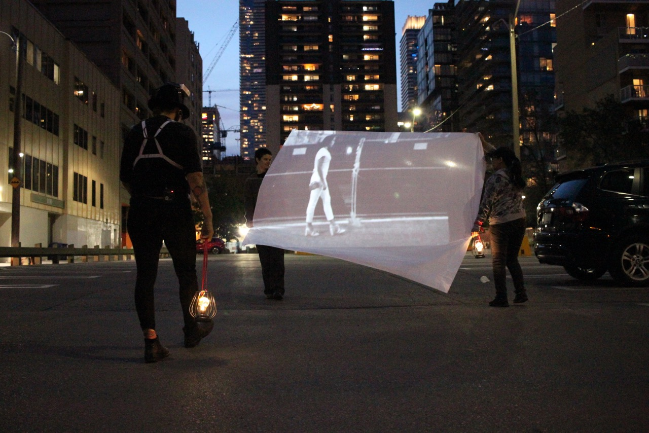 Two people are pictured holding up a white sheet with a projection of someone walking across in an urban parking lot. There is another person walking towards the projection wearing head equipment and all black, carrying a lamp in their right hand. There are different high rise buildings in the background, surrounding them.