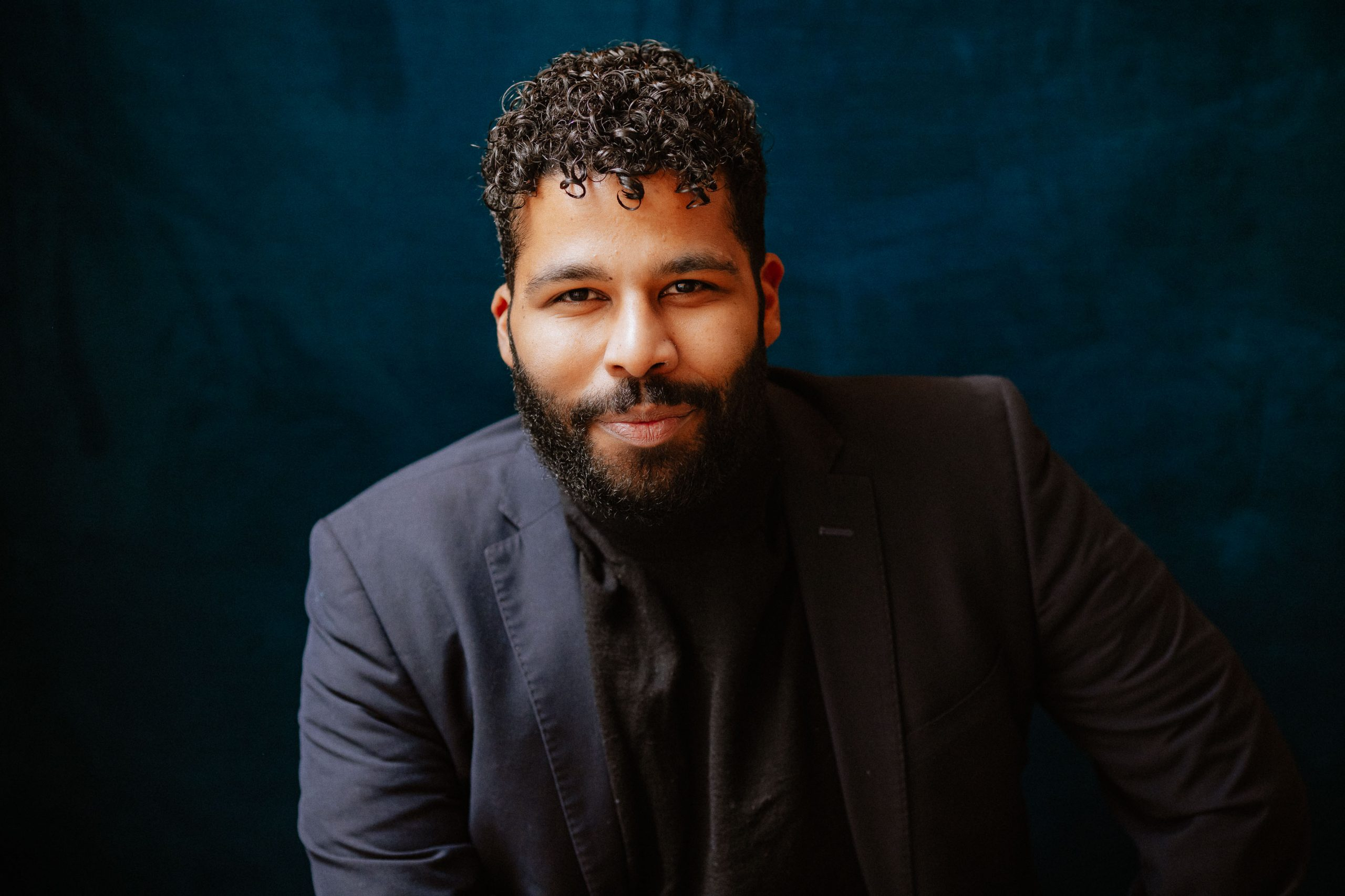 Jordan is wearing a navy blue suit jacket and black shirt. His hair is black with shaved sides and short curly hair on top, a few tendrils falling onto his forehead. Jordan's facial hair; a full beard and mustache, is dark brown/black. He is sitting in front of a navy suede background.
