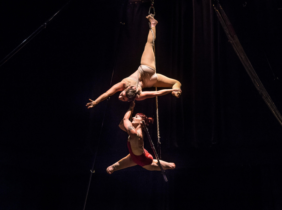 Suspended in the air, wrapped in the ropes above a trapeze bar that hangs from the ceiling, Erin, a white femme with no lower legs, splits her legs and smiles, just above the bar. Vanessa, a white woman, is upside down above Erin, hanging by one leg. The two wear outfits that match their skin and Erin's has some red in it.