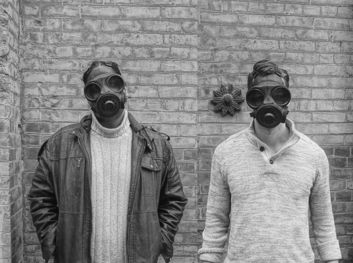 Two people pictured in gas masks in front of a brick wall in monochrome. To the left Jiv is pictured in a knit sweater with a leather jacket on top, Tom is pictured to the right in a knight sweater with their sleeves rolled up a bit. There is a clay flower just behind Tom to the left.