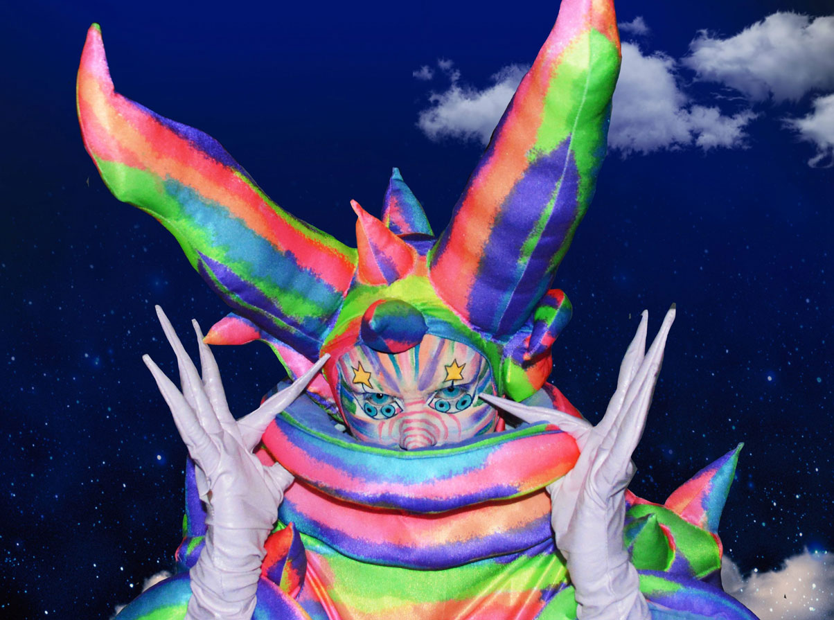 A drag queen dressed in a rainbow lizard costume