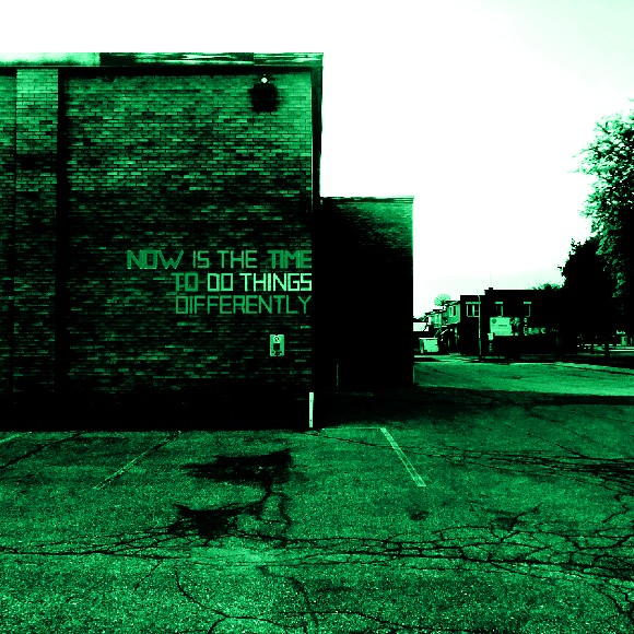 A brick building with NOW IS THE TIME DO DO THINGS DIFFERENTLY written on the side in colourful duct tape