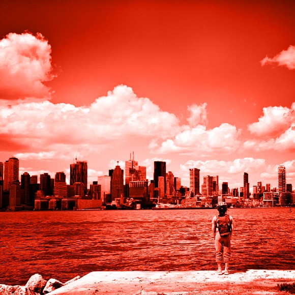 A child stands at the edge of a concrete slab looking across a small body of water towards a Toronto skyline full of many tall buildings