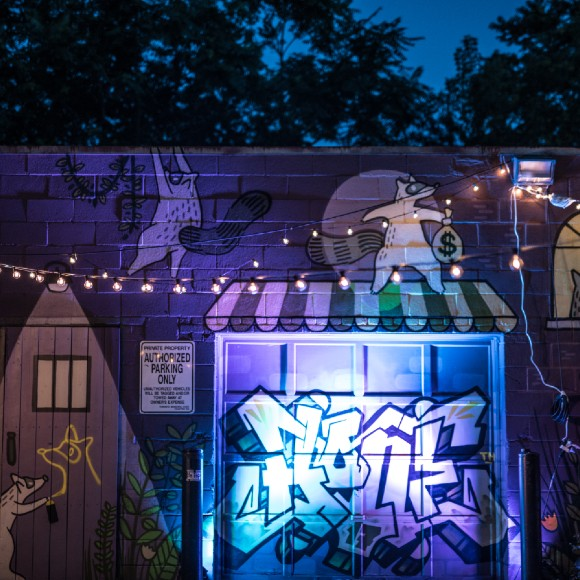 A courtyard at night decorated with strings of lights. A graffiti mural of houses and raccoons is in the background