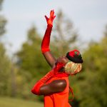 A black woman in a red dress and long red gloves reaches upwards