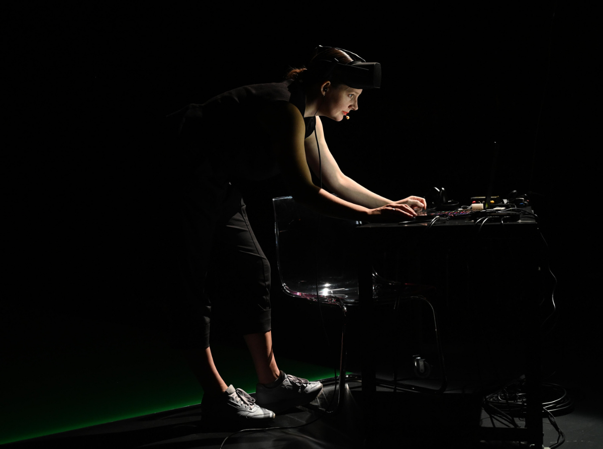 Freya is photographed on stage, bending over a desk looking into a laptop. There is a black table with wires coming down behind the desk and a black chair shining from a spotlight on top. Freya has a AR helmet while wearing all black and grey runners. The floor is black with a green screen showing behind.