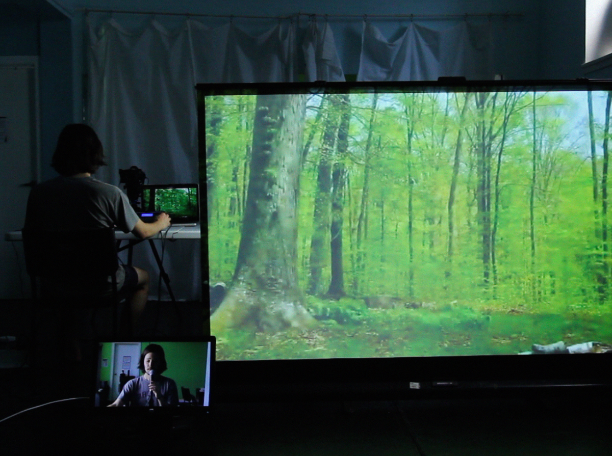 Phillip sits at a table with his back facing the camera, on the left side of a dark room. On the table, there is a computer and camera facing him. On the right side of the room, a large projector screen shows a picture of a lush green forest. In the background, there is a white door on the left side, a white drop sheet in the middle, and a production spotlight on the right side. In the foreground, a monitor shows Phillip in front of a green screen with a white door and various pieces of equipment behind him.