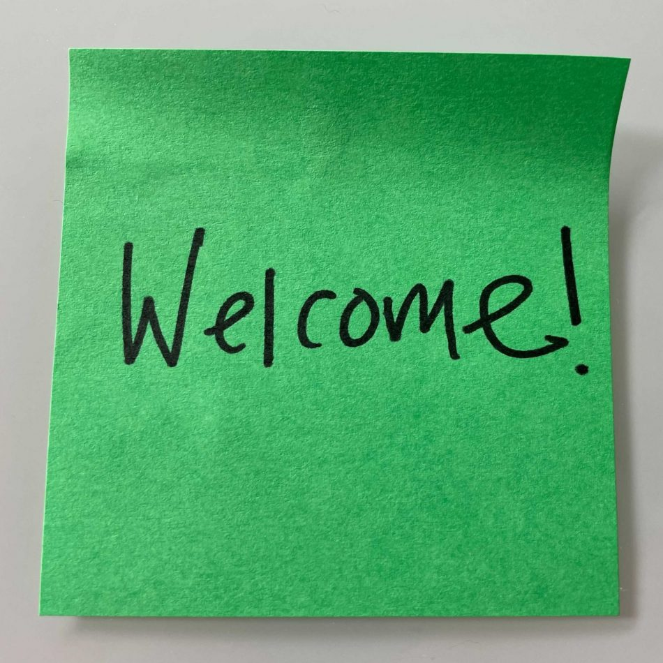 """A bright green sticky note with """"Welcome!"""" written in black marker."""
